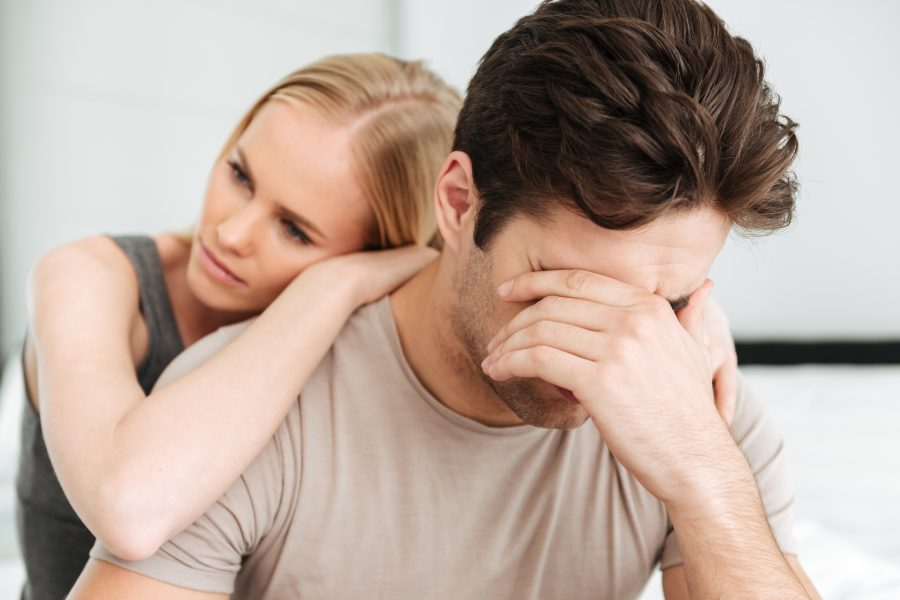 Carefree blonde woman comfort her sad crying man while they sitting in bed at home